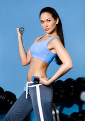 Athletic woman works out with dumbbells in training gym