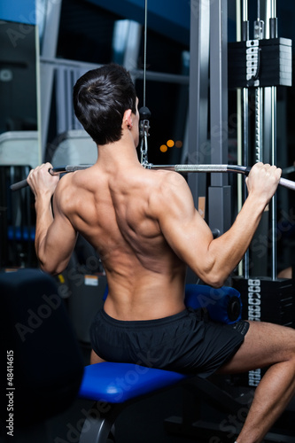 Athletic young man works out on simulator in fitness gym