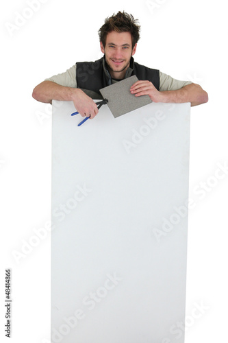 tiler holding an ad board