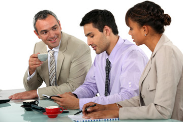 Three businesspeople discussing over coffee.