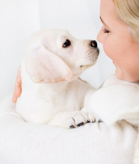 Close up of woman in white sweater embracing white puppy