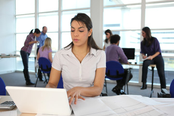 Woman using a laptop in a spacious office