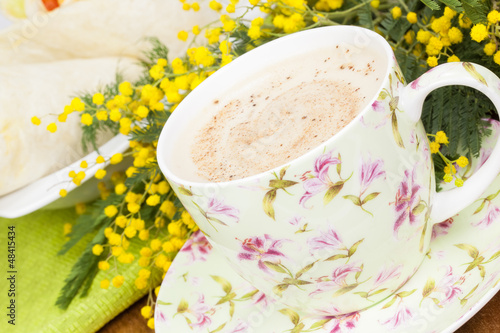 Cup of coffee on spring background