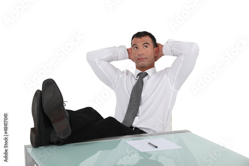 Businessman resting feet on desk