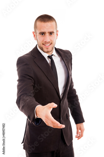 Smiling young businessman with an open hand ready to seal a deal