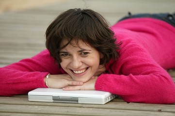 Brunette laying on jetty with laptop