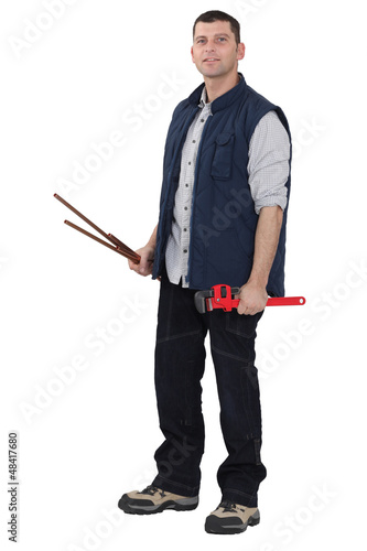 Man holding a pipe wrench and copper pipes