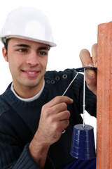 handsome bricklayer fixing bell on brick wall
