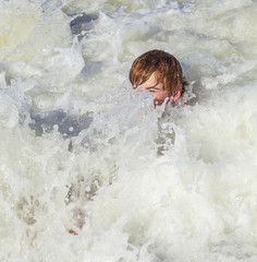 child has fun in the waves