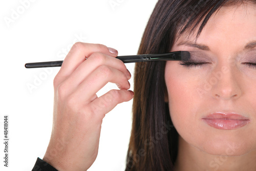 beautiful woman putting some eye shadow