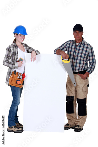 craftswoman and craftsman posing next to a blank poster