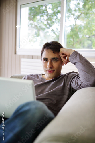 Young man on a sofa with a laptop
