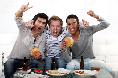 three friends eating while watching television