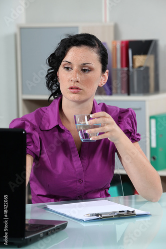 Office worker drinking water at her desk