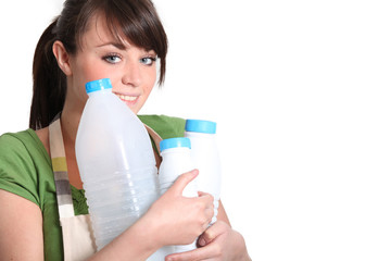 young woman carrying empty bottles of milk