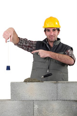 Bricklayer checking that wall is level