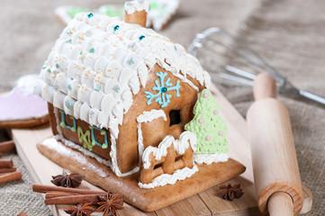 Gingerbread house and kitchen utensils, horizontal shot