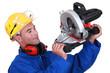 Construction worker examining his circular saw.