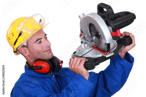 Construction worker examining his circular saw.