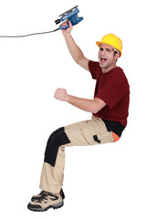 joyful carpenter holding sander machine