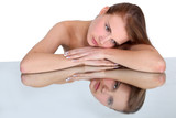 Woman resting head on reflective surface