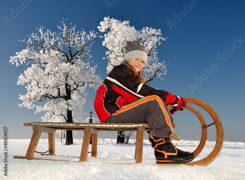 girl on a sleigh in winter landscape