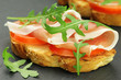 Italian bruschetta with prosciutto, rucola and tomatoes