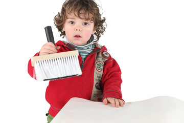 Young child holding a brush
