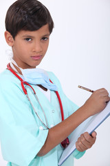 Little boy with chart dressed-up as doctor