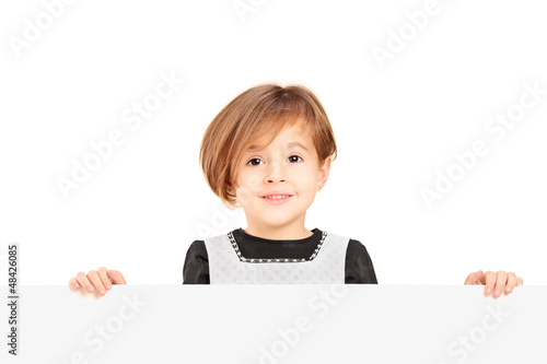 Little smiling girl standing behind a blank panel