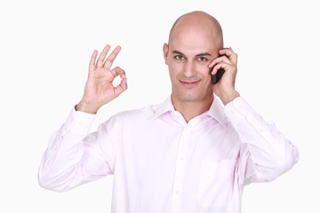 Man on phone doing OK sign