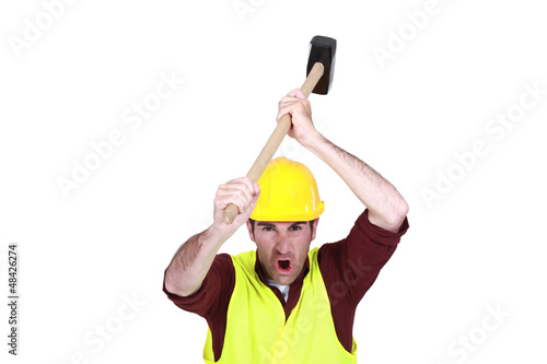 Construction worker about to bang an object with a mallet