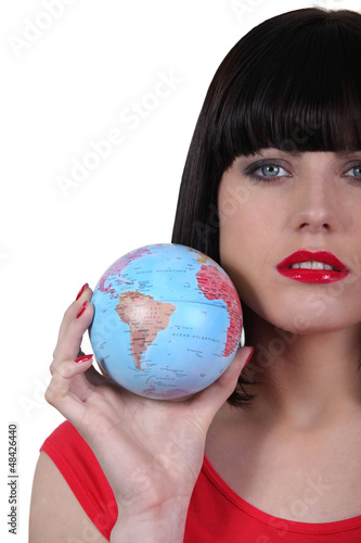 Serious beautiful woman with the world in her hand
