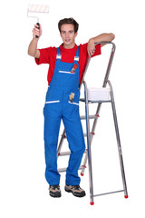 Decorator with a paint roller and stepladder