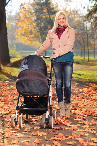 Mother taking a walk in park with her baby in a pushchair