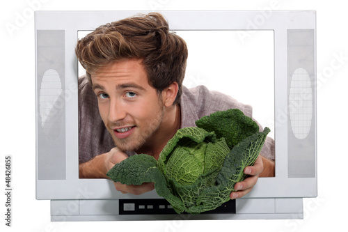 Man holding cabbage escaping from television