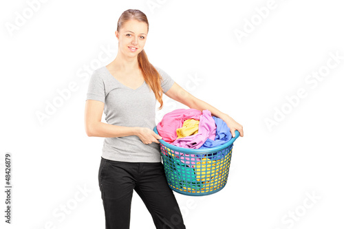Young woman standing and holding a laundry basket full of clothe