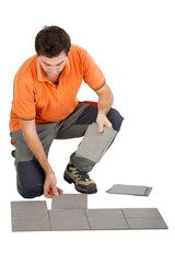 Man laying out tiles on the floor