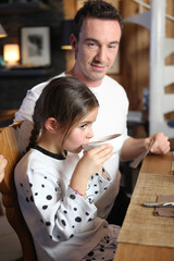 Girl drinking hot chocolate with her father
