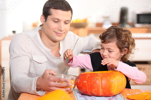 Dad and daughter hollowing out a pumpkin