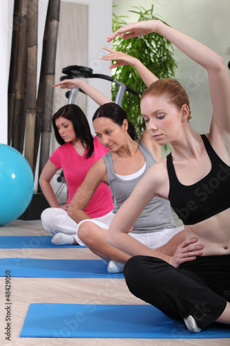 female threesome doing exercise indoors