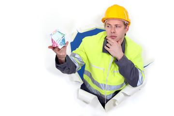 Pensive builder holding globe