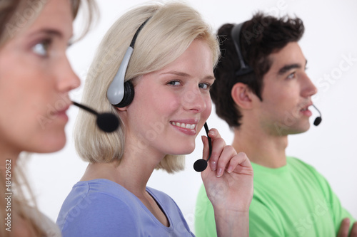 Three call-center workers sat in a row