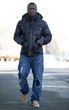 Dunkelhäutiger junger Man geht zu Fuß