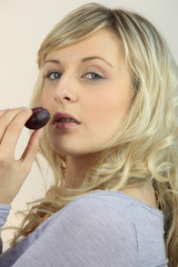 blonde woman eating a fruit