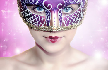 Woman in carnival mask over pink background