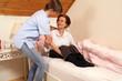 Pflegekraft hilft Seniorin beim Aufstehen