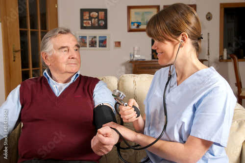 Pflegekraft misst Blutdruck bei Senior