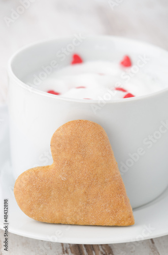 cup of hot milk with foam, decorated with sugar hearts and heart