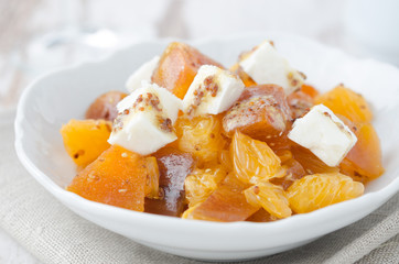 salad with persimmon, mandarin oranges and goat cheese closeup